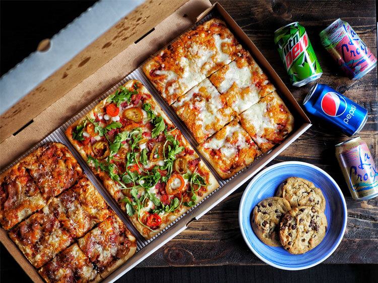 Formaggio Pizza, Italian Deluxe Pizza and Meatball Ricotta Pizza in a delivery box with a mountain dew can, a pepsi can, a Passion Fruit La Croix can and Grapefruit La Croix can as well as 3 chocolate chip cookies .