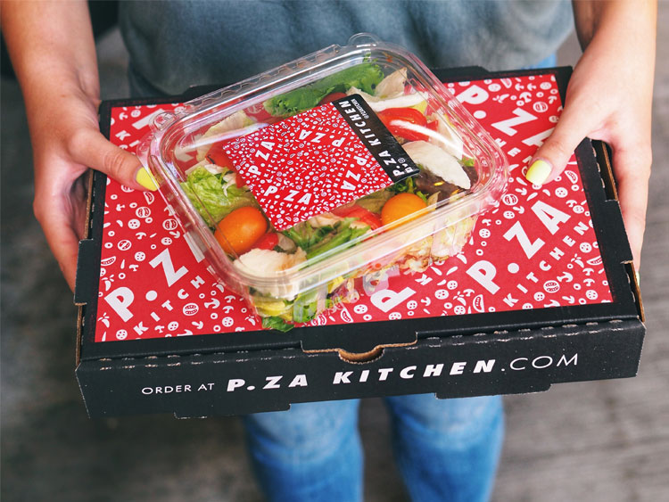 Person holding P.Za Kitchen Delivery Pizza Box and Salad Tin.